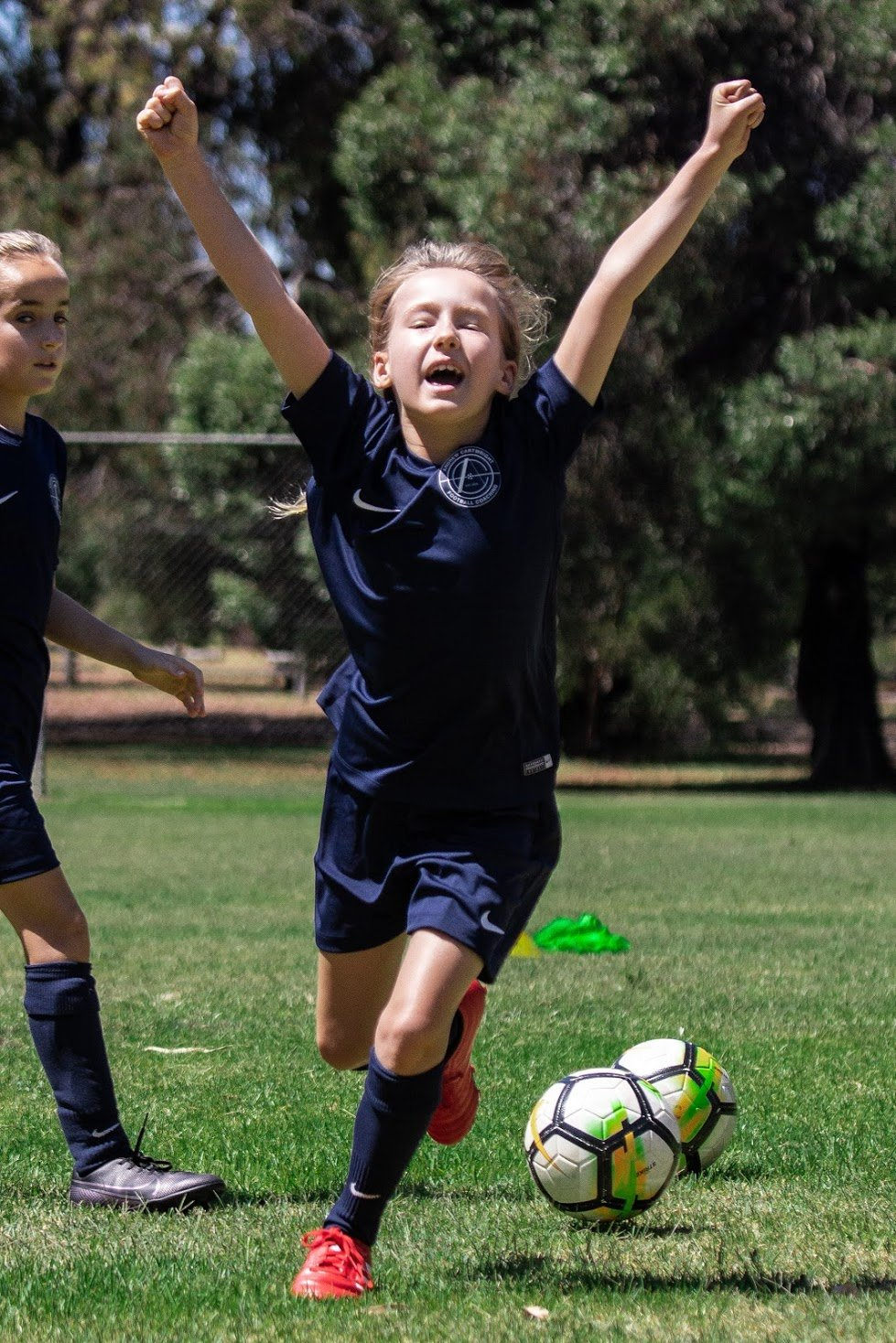girl footballer running with her arms raised in the air