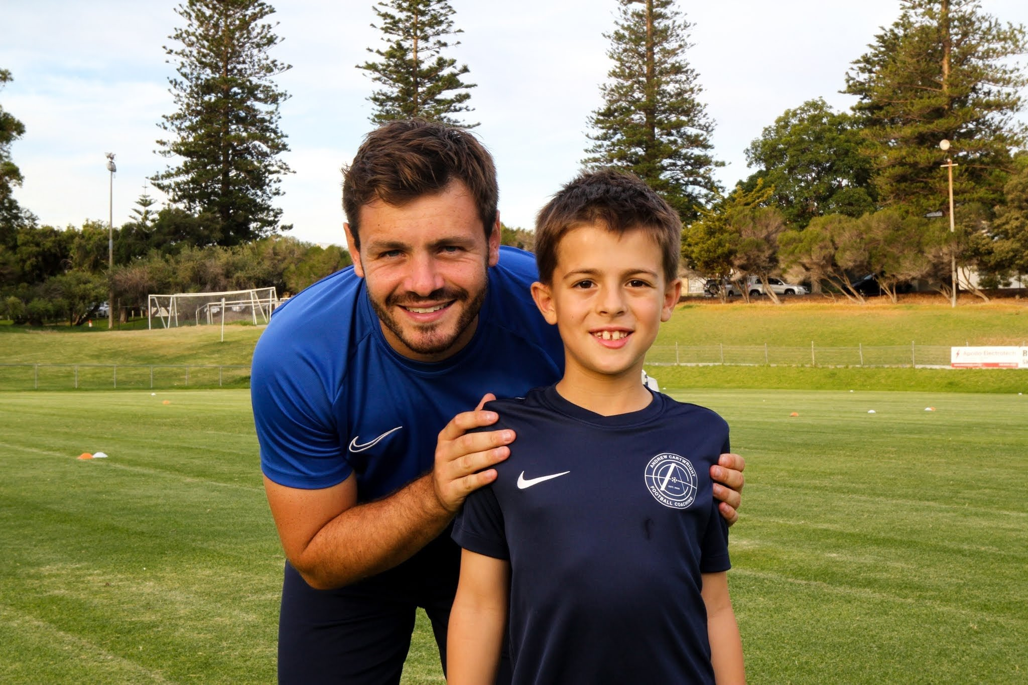 Andrew Cartwright standing next to young boy footballer