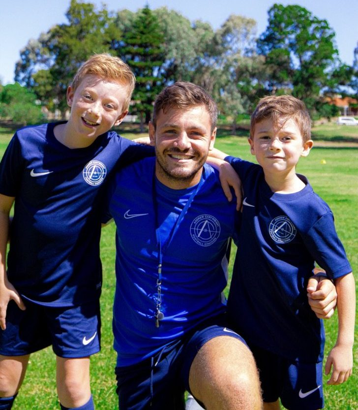 andrew cartwright kneeling between 2 young boy footballers