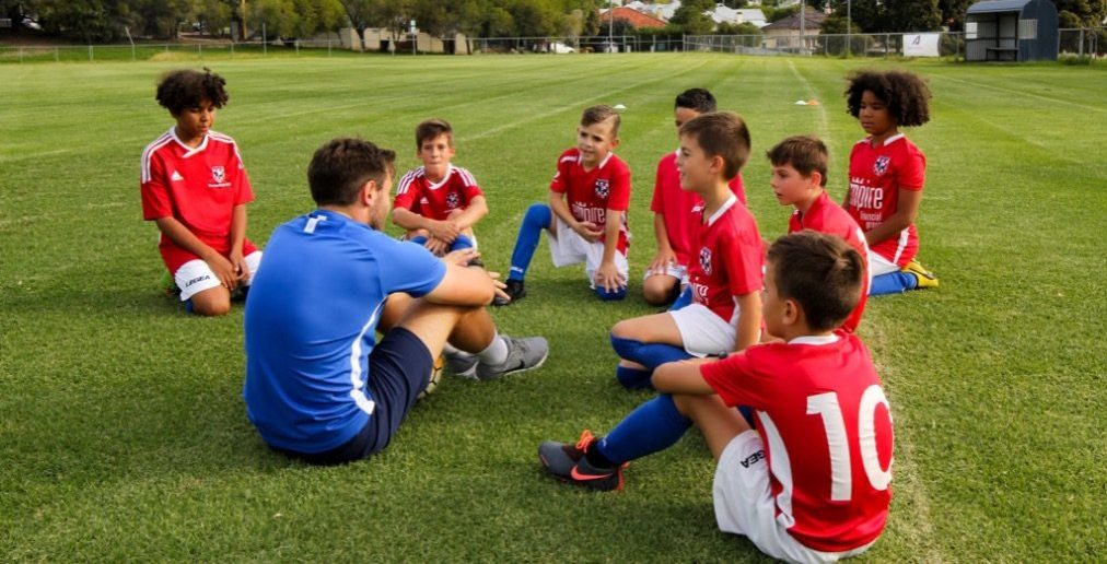 andrew cartwright sitting down with a group of young footballers